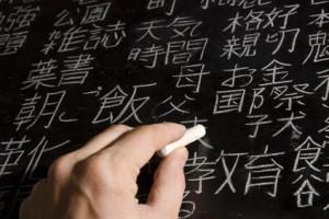 Mann schreibt mehrere japanische und chinesische Zeichen an eine Tafel