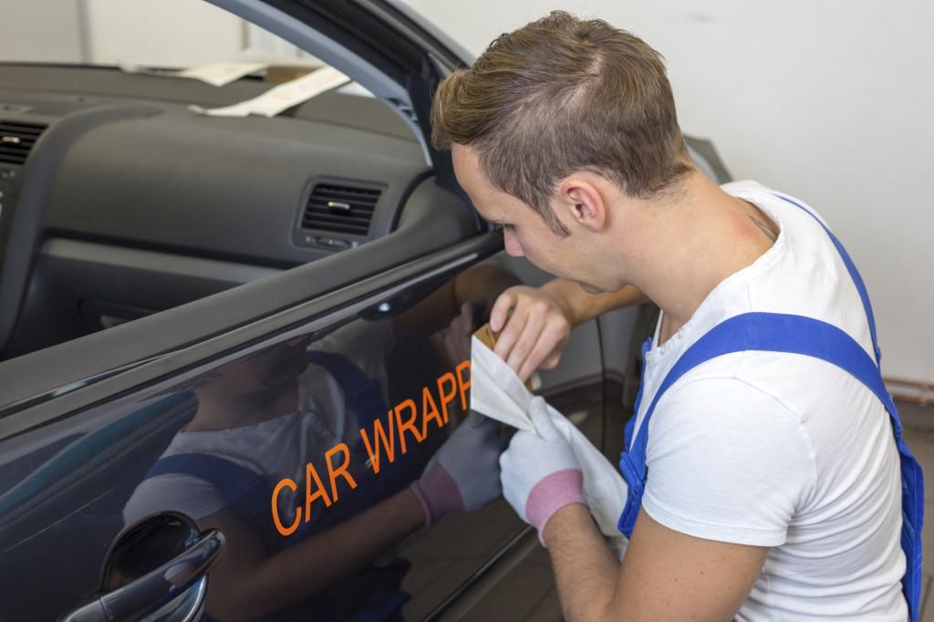 Mann beklebt Auto